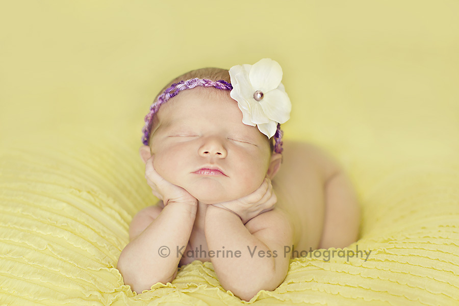 cute newborn with chin in hands pose
